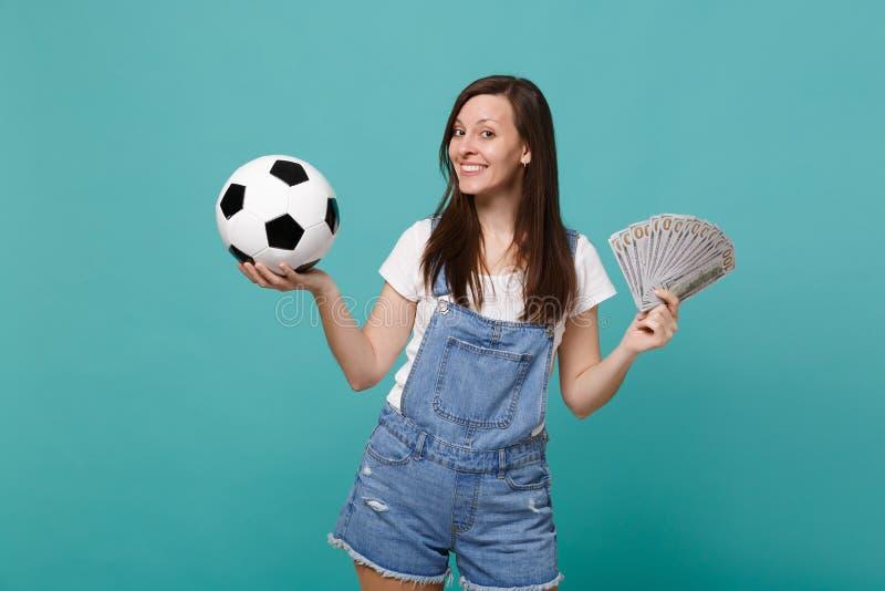与足球的微笑的年轻女人足球迷支持喜爱的队,金钱在美元钞票,现金金钱爱好者  库存图片