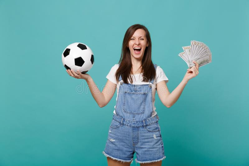与足球的笑的年轻女人足球迷支持喜爱的队,金钱在美元钞票,现金金钱爱好者  免版税库存图片