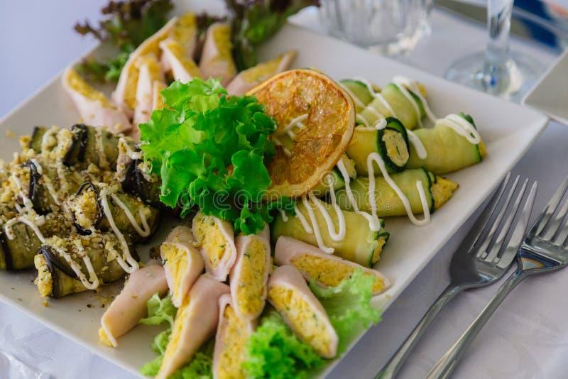 与芝麻菜和夏南瓜卷的沙拉在板材,在桌背景 库存图片