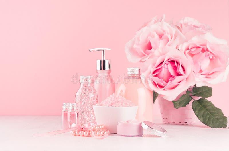 与花,化妆用品产品的柔和的少女梳妆台-玫瑰油、腌制槽用食盐、奶油、香水、棉花毛巾、瓶和弓 库存照片