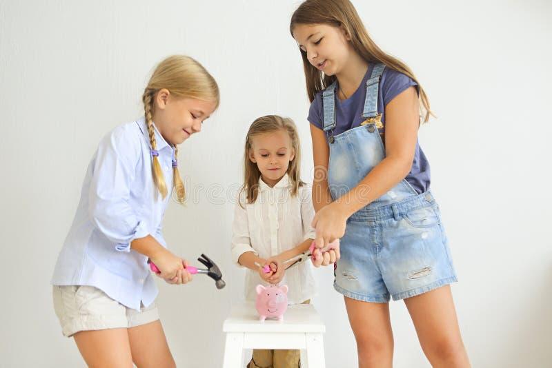 与螺丝刀、钳子和锤子的孩子由桃红色猪存钱罐 图库摄影