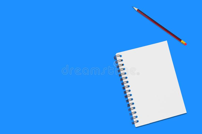 与螺旋黏合剂的一个纸笔记薄和在蓝色办公室桌附近木铅笔谎言的空白纸  顶视图 事务的概念 库存图片