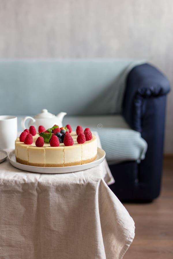 与莓果的奶酪蛋糕与茶壶和杯子在休息室 库存照片