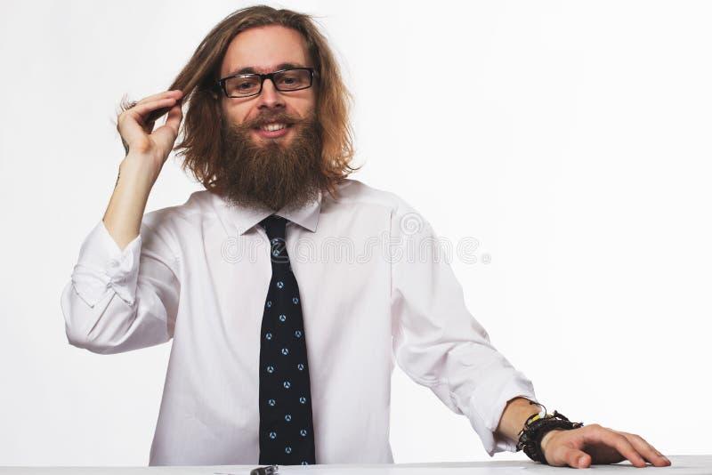 与胡子的认为在白色墙壁上的桌上的英俊的年轻商人和玻璃 免版税库存照片