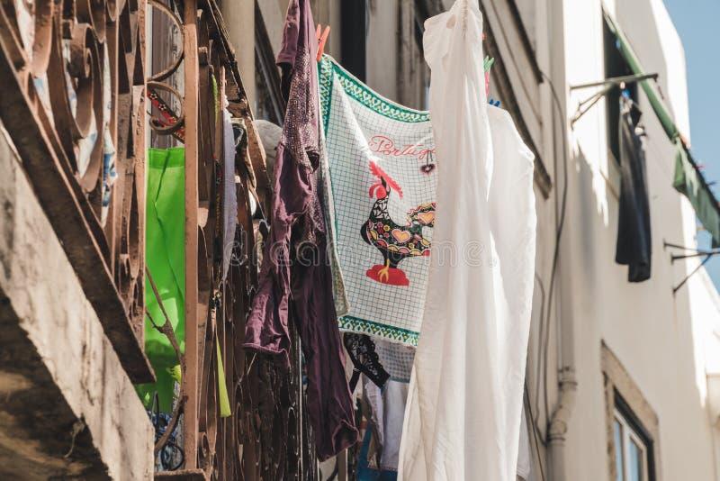 与葡萄牙的典型的雄鸡的一块旧布在里斯本的阳台的干燥洗衣店旁边垂悬  免版税库存图片