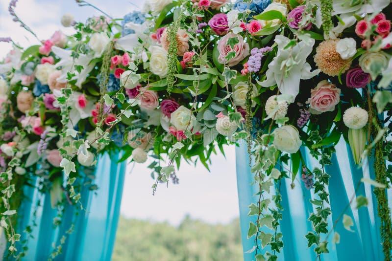 与蓝色布料的花卉装饰婚礼的 与美丽的花的婚礼曲拱 免版税图库摄影
