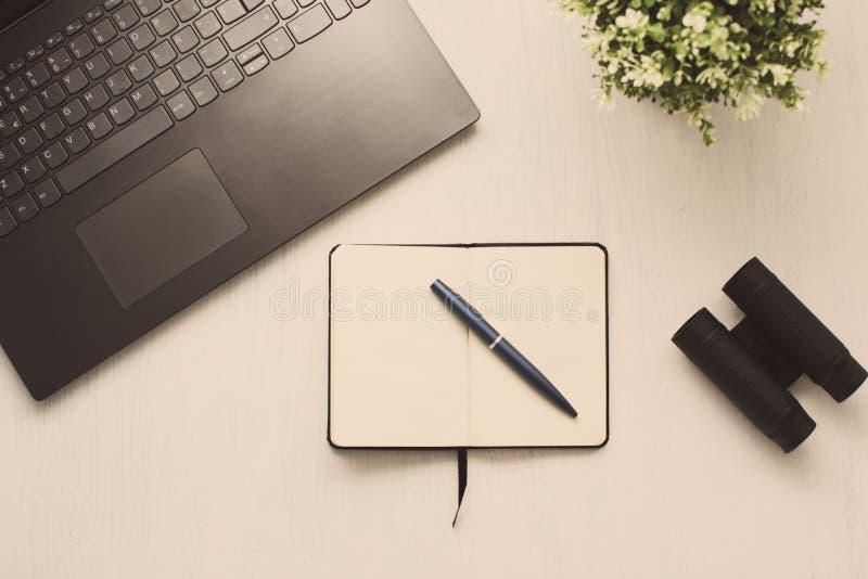 与膝上型计算机的平的被放置的台式、植物,双筒望远镜、笔和笔记本或者日志 网或互联网查寻概念 免版税库存照片