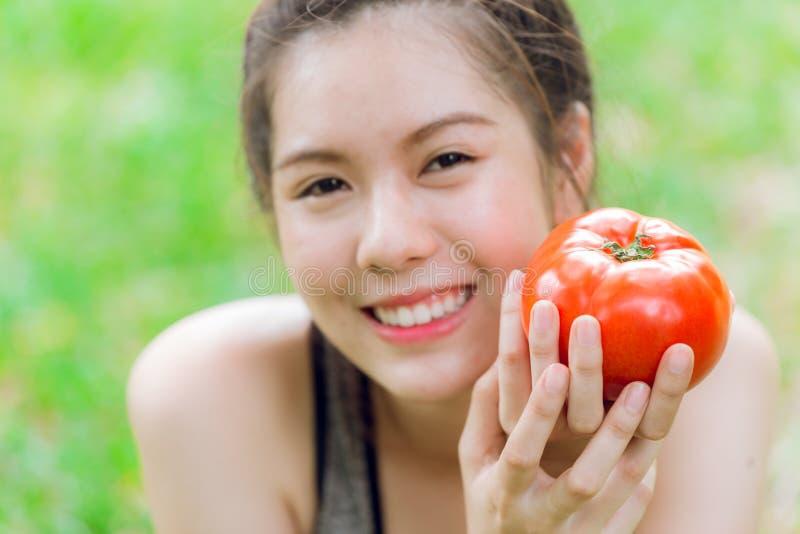 与蕃茄微笑愉快的好健康皮肤的青少年 库存图片