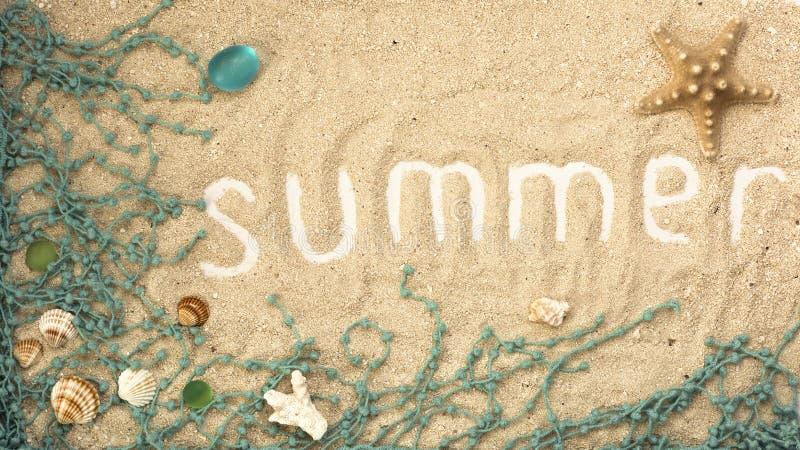 与贝壳和细节的夏天题字在含沙背景 flatlay的夏天 库存图片