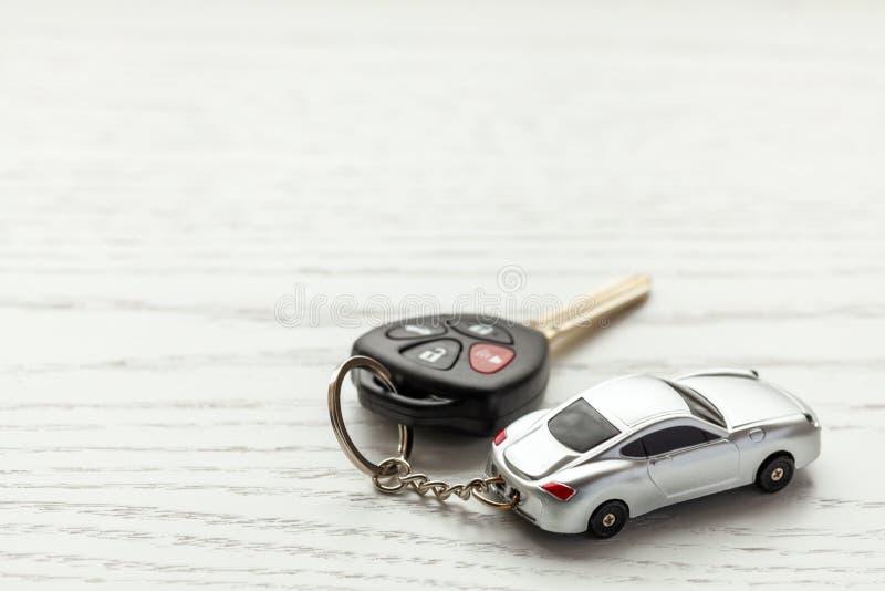 与遥控安全和汽车钥匙链的汽车钥匙在白色木背景 复制文本的空间 免版税图库摄影