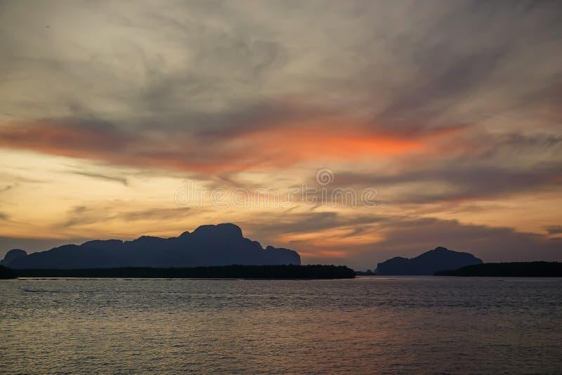 与高山与被阐明的峰顶,石头在山湖,反射、天空蔚蓝和黄色阳光的美好的风景 免版税图库摄影