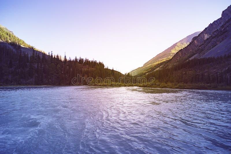 与高岩石与被阐明的峰顶,石头在山湖,反射、天空蔚蓝和黄色阳光的美好的风景 免版税库存照片