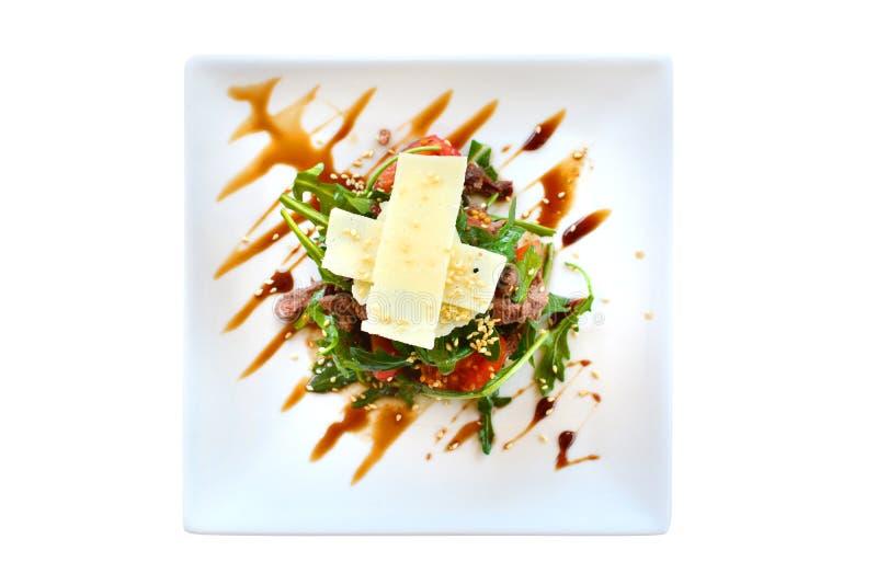 与鸭胸脯、绿色、西红柿、葡萄和桔子的沙拉,洒与在一块白色板材的芝麻,隔绝在白色 免版税库存图片