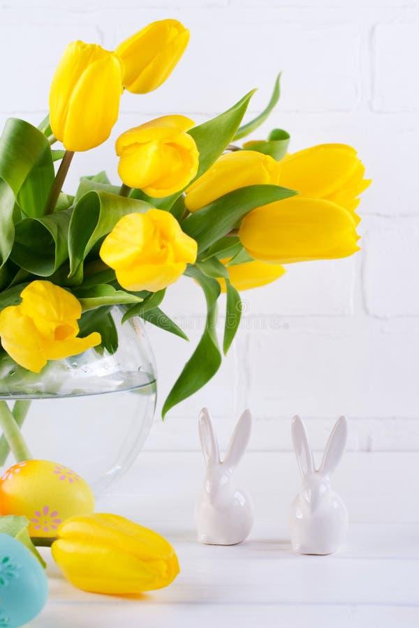 与黄色郁金香花花束的复活节构成在玻璃花瓶和两只白色陶瓷兔子的在白色 免版税库存照片