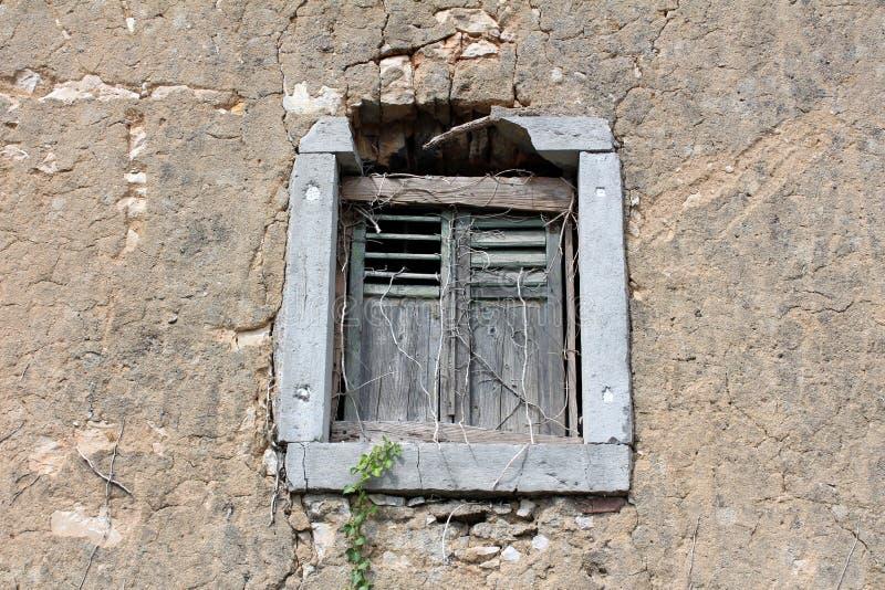 与闭合的窗帘的被毁坏的残破的老木窗口在被放弃的家庭房子废墟部分地长满与烘干 库存图片