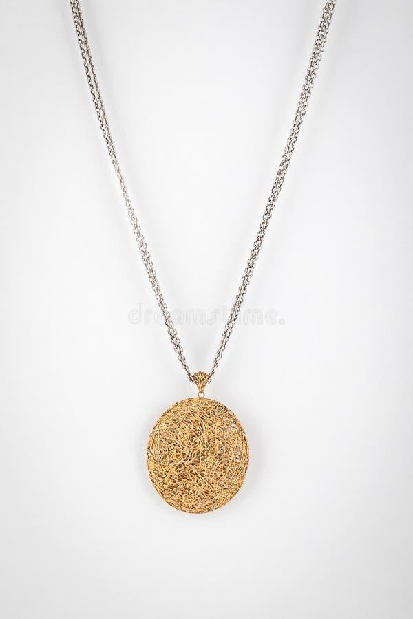 与金子的银色链子把下垂n编成辫子以在白色背景隔绝的球的形式 图库摄影