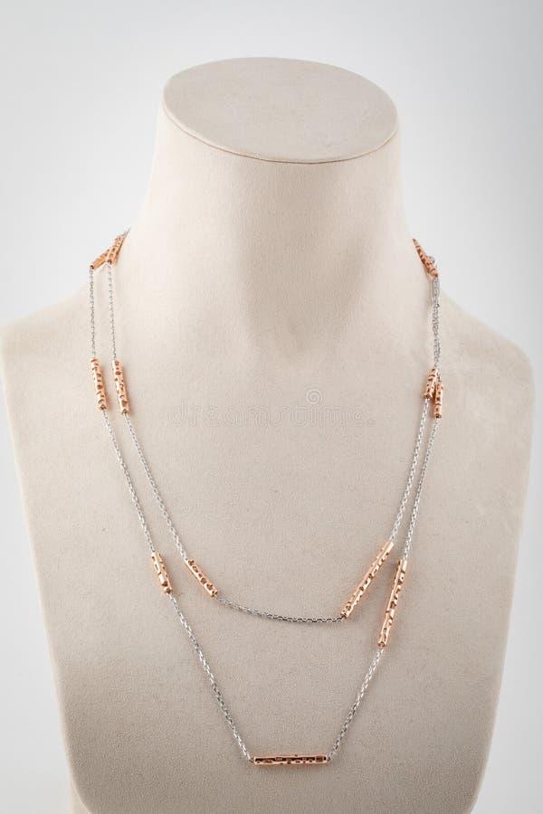 与金插入物的妇女银色双重链子在白色时装模特 免版税库存图片