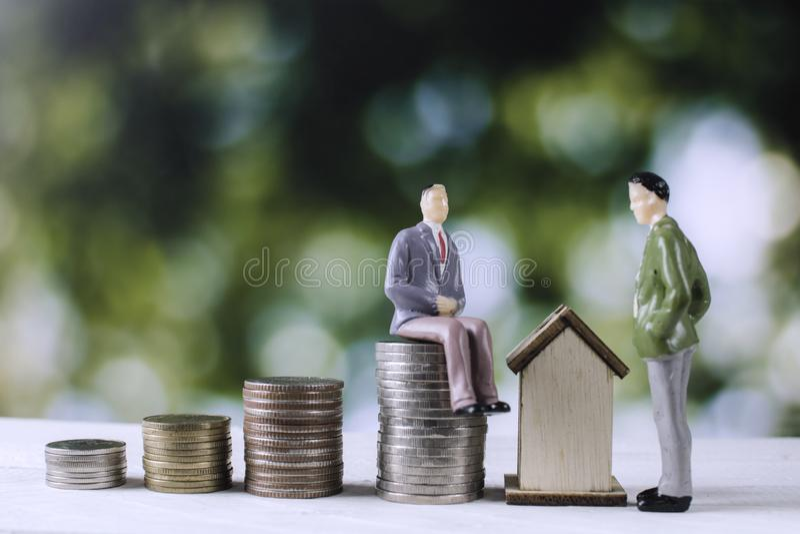 与金钱硬币和房子的商人模型 库存图片