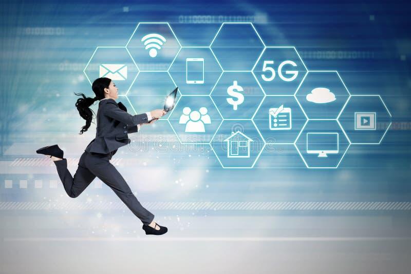 与5G网络系统的女实业家赛跑 库存照片