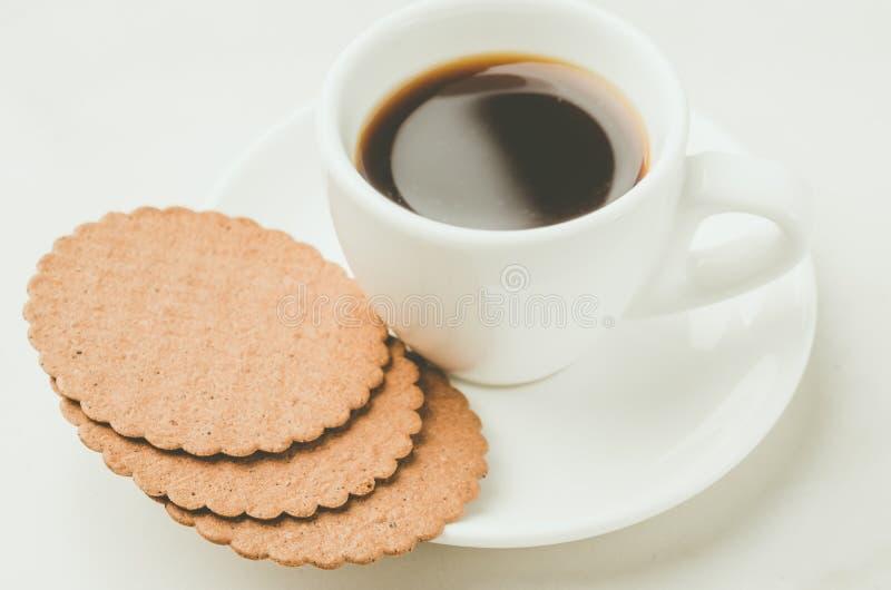 与Coffe浓咖啡白色杯子的早餐用曲奇饼/与Coffe浓咖啡白色杯子的早餐用在白色背景的曲奇饼 库存照片