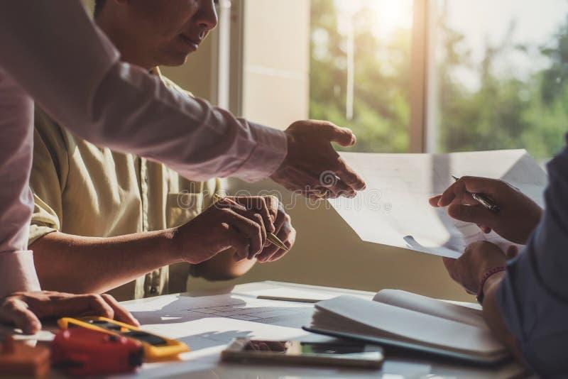 专业建筑师工作大楼计划设计项目队与图纸和工程学工具的在设计事务所 免版税库存图片