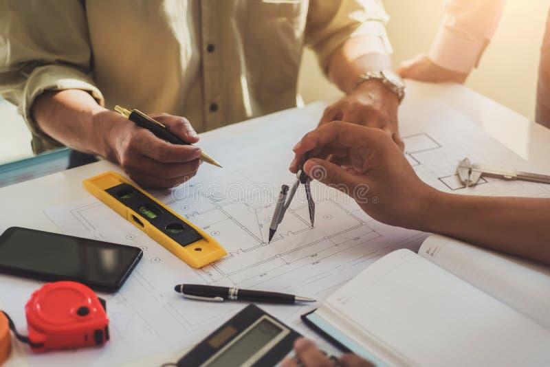 专业建筑师工作大楼计划设计项目队与图纸和工程学工具的在设计事务所 免版税库存照片