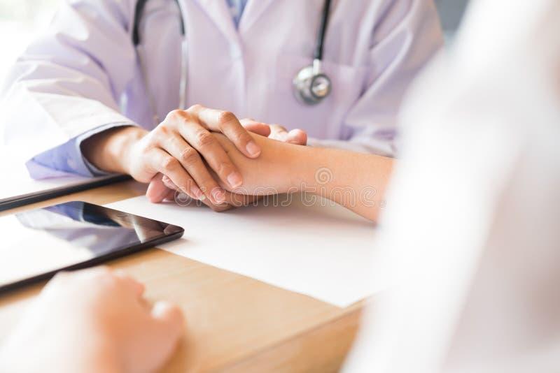 专心地听一位男性医生的患者解释耐心症状或问问题,他们一起谈论文书工作  库存图片