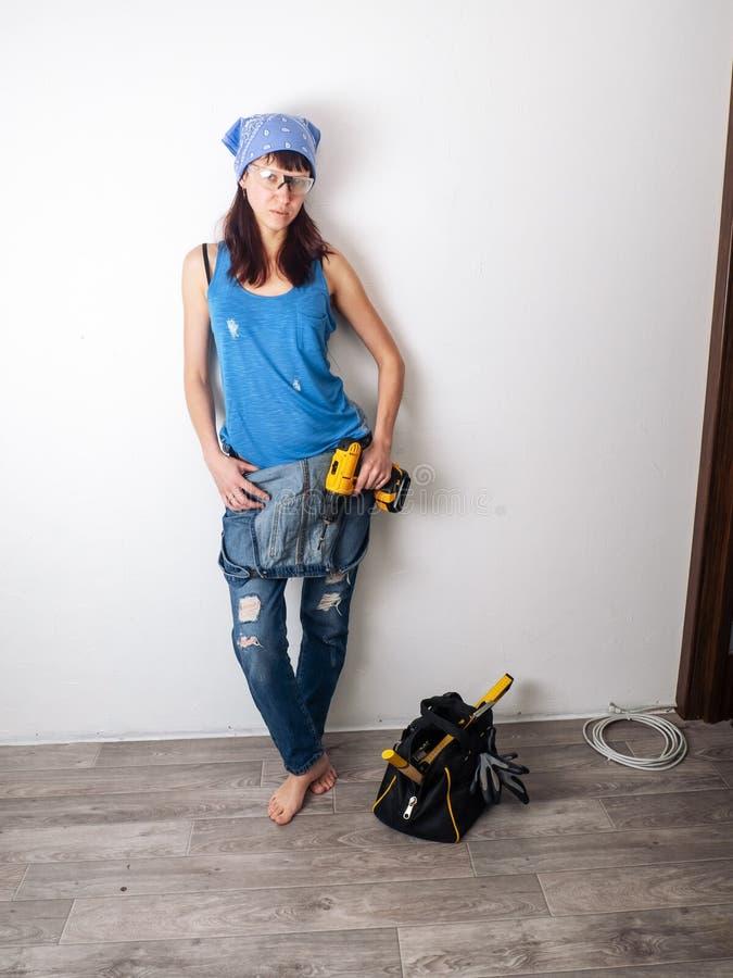 万能博士在她的手上站立对白色墙壁并且拿着一把黄色螺丝刀的性感女孩 一个工具 免版税库存照片
