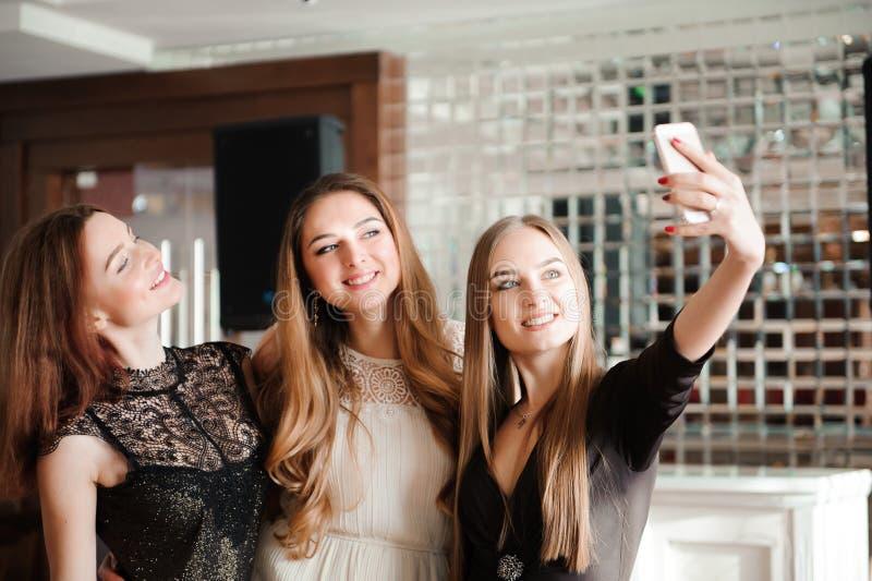三个女孩在餐馆做着selfie照片 免版税库存图片