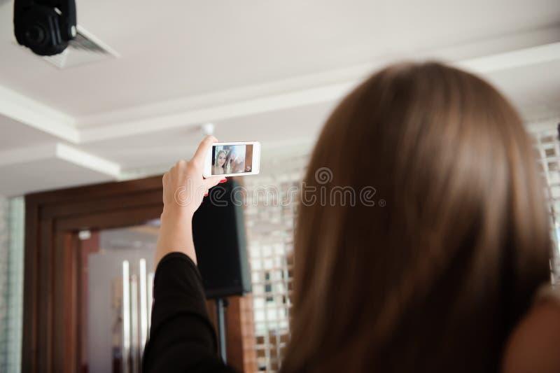 三个女孩在餐馆做着selfie照片 库存图片