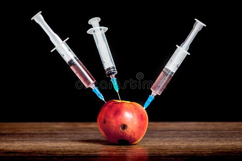 三个注射器被插入入与腐烂踪影的苹果 药物的收养 毒瘾的问题 密集的therapy_ 免版税库存照片