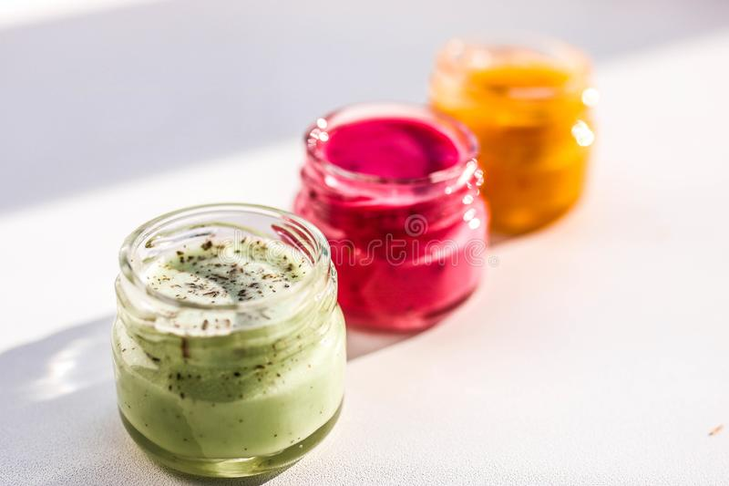 三个瓶子五颜六色的果酱 绿色红色和yeallow蜂蜜蛋白牛奶酥 免版税库存照片