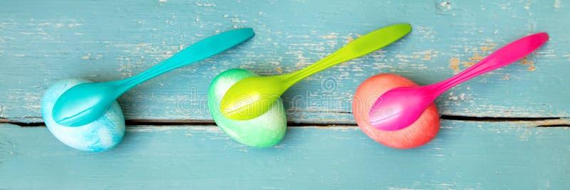 三把五颜六色的被洗染的复活节彩蛋和蛋匙子在蓝色木背景 免版税库存图片