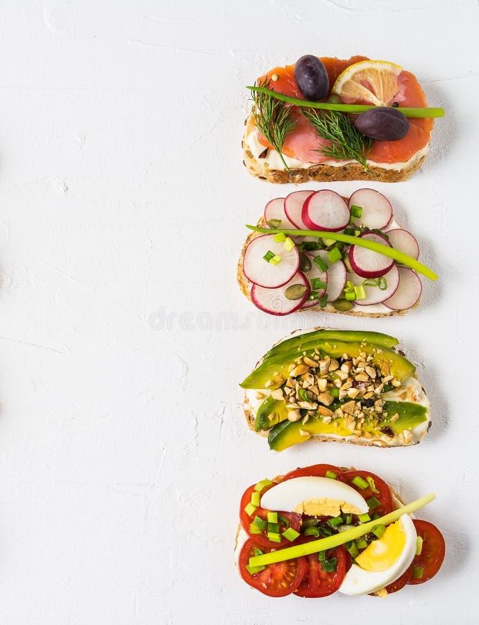 三明治准备与奶油奶酪和菜和三文鱼,在一块板材,在餐巾 健康食品午餐或早餐 库存图片
