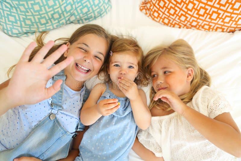 三愉快在获得的床上的妹乐趣 库存照片