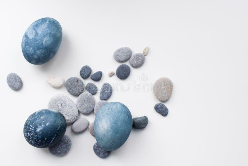 三色的蓝色,灰色大理石鸡蛋在石头中的白色背景说谎 免版税库存照片