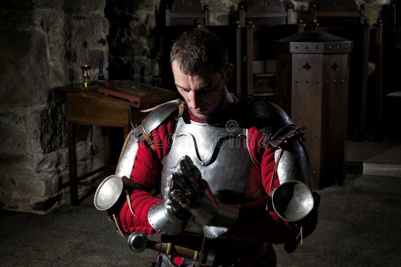 下跪在他的与低下的头和祈祷的手的膝盖的骑士 图库摄影