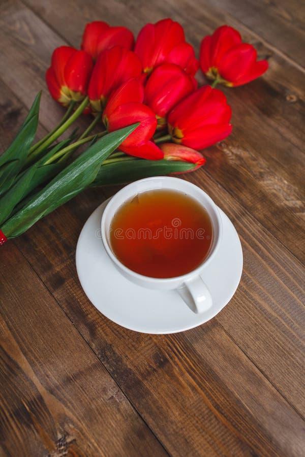下雨 红色郁金香花束与茶杯的在棕色木背景 母亲节和情人节概念 免版税库存照片