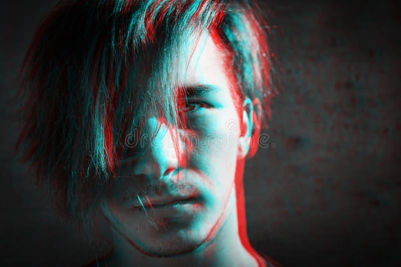 一个严肃的人的画象有被弄乱的头发的在灰色混凝土墙背景 数字信号小故障作用rgb转移,切片 库存照片
