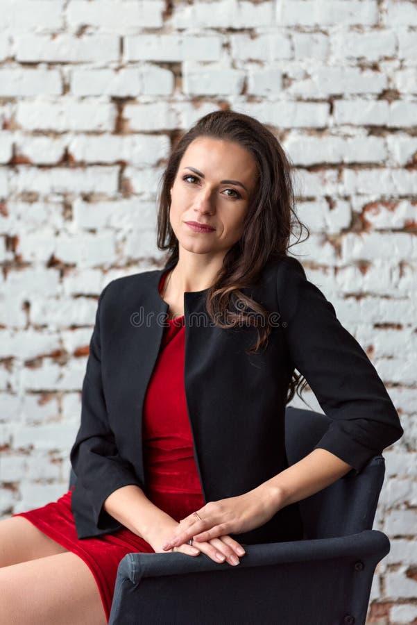 一个中年深色的女商人的画象一件短的红色礼服和黑夹克的坐与白色墙壁的一把椅子  图库摄影