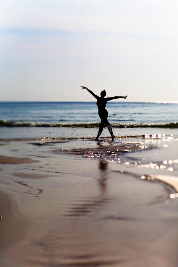 一个亭亭玉立的女孩的剪影以海为背景的 库存图片