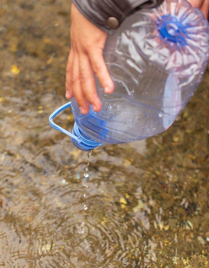 一个人从河积在瓶的水 库存照片
