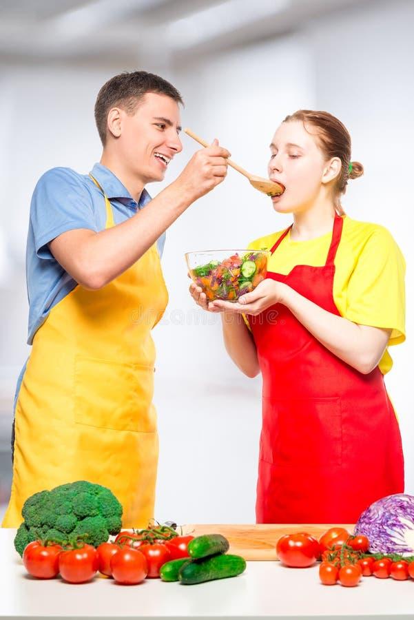 一个人对待女孩与新鲜蔬菜沙拉,他们一起烹调 免版税库存图片