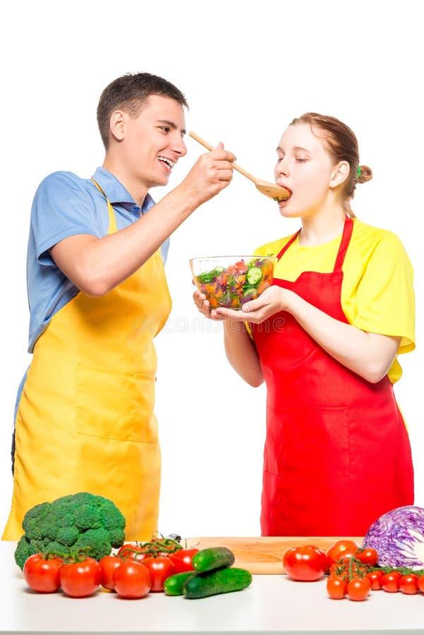 一个人对待女孩与新鲜蔬菜沙拉,他们在白色一起烹调 免版税库存图片