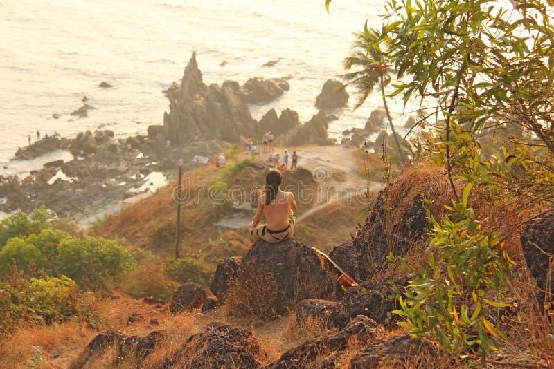 一个人在山和神色顶部入距离,在海和坐日落 孑然的一个人,单独与自然, 免版税库存照片