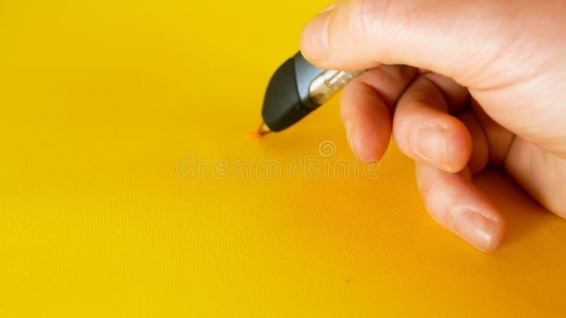 一个人的手画与在黄色背景的一支3d打印机笔,题目的英尺长度理想例如创新,技术 图库摄影