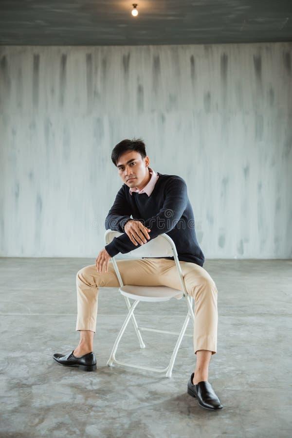 一个偶然商人的姿势坐一把白色椅子在大厅里 免版税库存图片