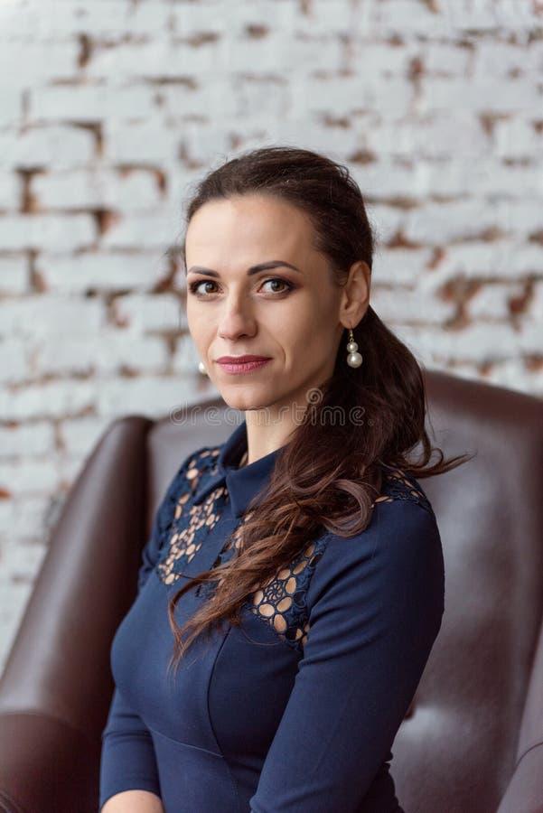 一个可爱的女商人的特写镜头画象一件蓝色礼服的举行了后面微笑和坐扶手椅子 免版税库存图片