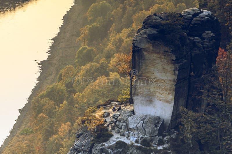一个大岩石的风景在背景中与村庄和森林前景的在秋天在阳光 图库摄影