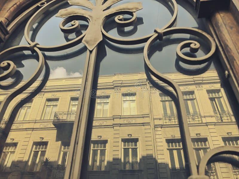 一个大厦的反射在街道上的在与铁装饰装饰品的玻璃木门 老第比利斯建筑学 库存照片